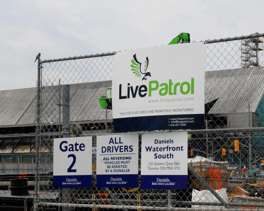 Safety signs attached to a fence on a construction site