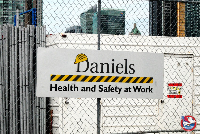 Aluminum sign with the Daniels Corporation branding mounted on a fence on a construction site